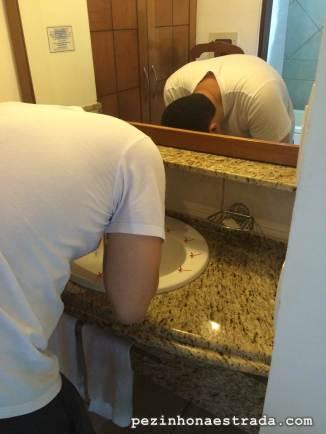 Marido lavando o rosto, mas vejam só as florzinhas estrategicamente distribuídas na pia. Uma coisa legal é que a pia fica separada da área onde tem o vaso e chuveiro, o que deixa mais prático para quem está dividindo o quarto com muita gente. Hotel Tibau Lagoa