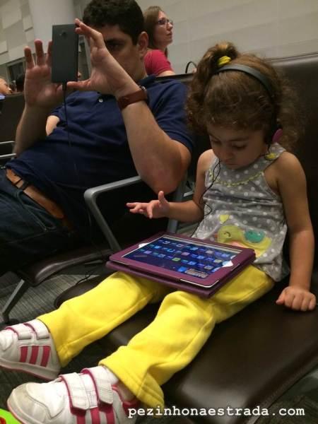 Papai e Bela recarregando seus respectivos eletrônicos e passando tempo na sala de embarque do Aeroporto de Viracopos (sim, eles têm tomadas!)